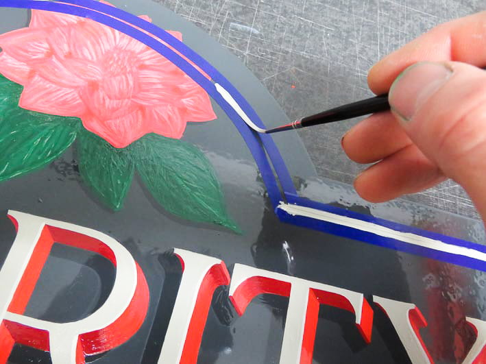 Painting inlines around the hand lettered sign