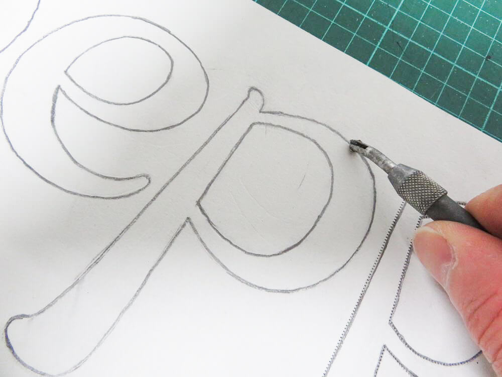 following the lettering with a pounce wheel
